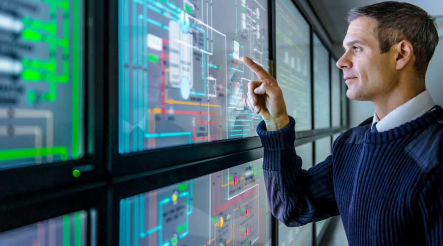 Facilities manager using energy monitoring software on a multiple screen view, industrial energy management.